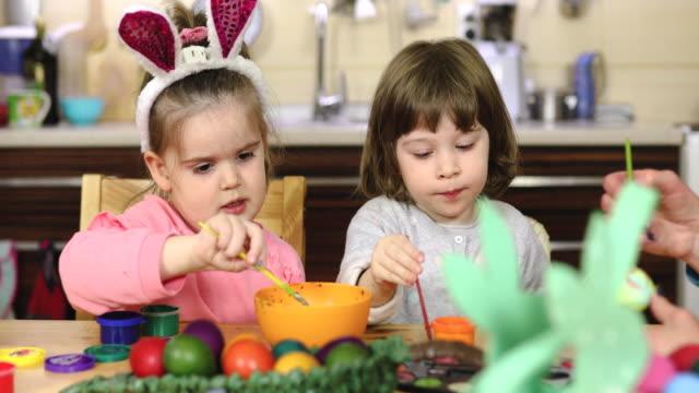 vídeos de stock e filmes b-roll de creative toddler girls preparing paint for easter egg decoration - domingo de páscoa