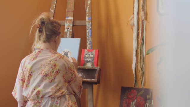 creative woman paints pictures of animals at easel in her home - canvas stock videos & royalty-free footage