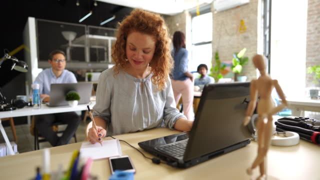 stockvideo's en b-roll-footage met creatieve vrouw werkzaam op kantoor - natuurlijk haar
