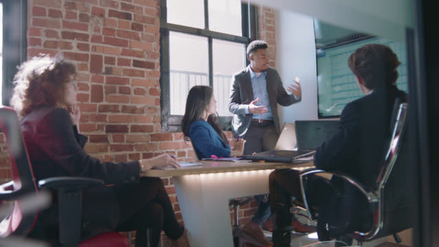 creative young african-american businessman leads team meeting, points to data on monitors, discusses ideas with coworkers - busy stock videos & royalty-free footage