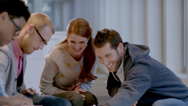 creative young business people write and laugh around white-board table in large corporate office common area (dolly shot) - business relationship stock videos and b-roll footage