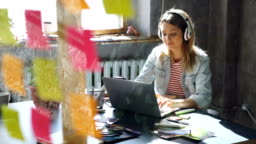 Creative young businesswoman is listening to music in headphones dancing while working at desk with laptop in modern office. Glass with colored stickers in foreground.