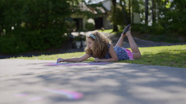 vidéos et rushes de ls creative young girl happily lays on the grass and draws a colorful rainbow on her driveway with chalk - trottoir