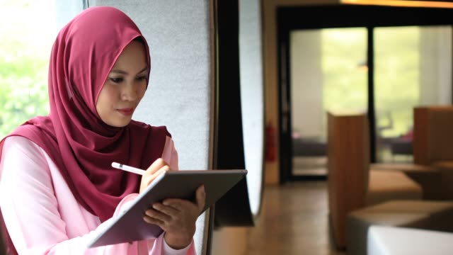 creative young muslim woman working on digital tablet in modern office - graphics tablet stock videos & royalty-free footage