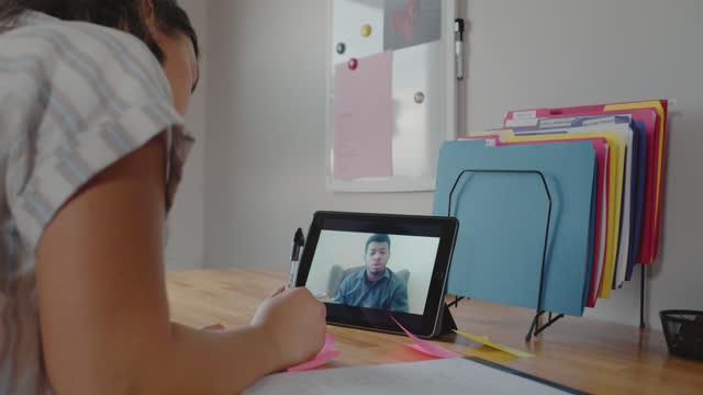 creative young woman jots down notes on a sticky note and posts on a whiteboard as she video chats with a colleague - digital tablet stock videos & royalty-free footage