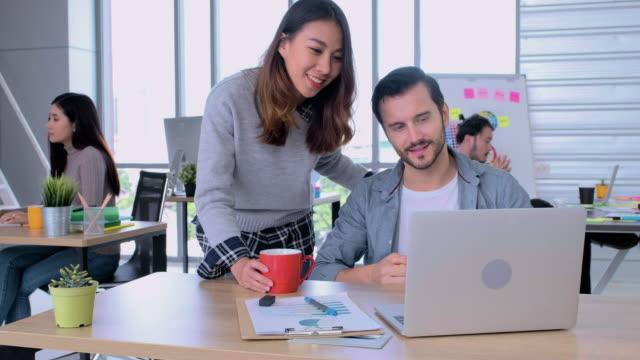 vídeos de stock, filmes e b-roll de escritório de negócios creatvie, designer de mulher asiática tomar uma xícara de café ao colega que o estresse do trabalho no laptop na mesa, amigo de incentivar - consolar