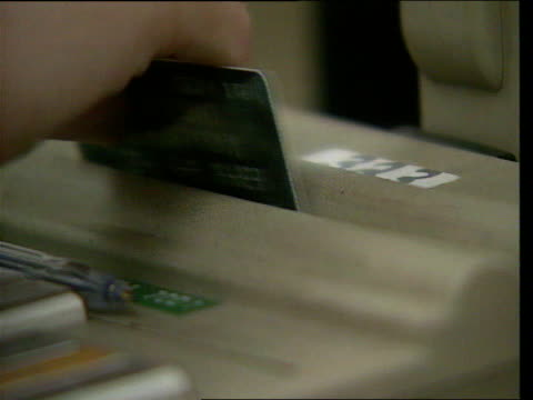 Credit card fraud LIB London Marks Spencer Sales assistant swiping credit card through machine then repeating swipe CMS Line of cash register display...