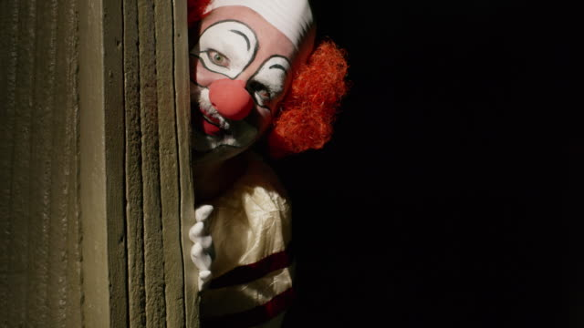 vidéos et rushes de creepy clown peering around dark corner licking lips / cedar hills, utah, united states - coin