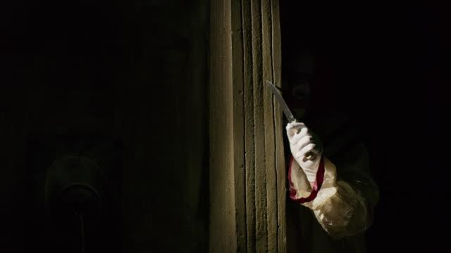 Creepy clown peering around dark corner waving knife / Cedar Hills, Utah, United States