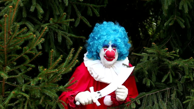 creepy clown with knife hiding in trees - clown stock videos & royalty-free footage