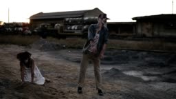 Creepy two zombies in bloody clothes walking through the ruined city during the zombie apocalypse. Abandoned place with trucks on the background