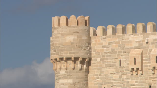 Crenelations top a fortress tower and wall in Alexandria, Egypt.