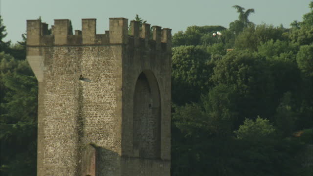 A crenellated parapet towers over a bridge in Italy.