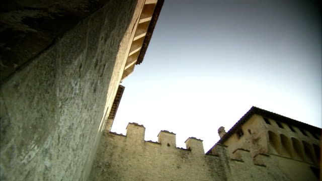 Crenellations top the towering walls of a castle in Italy. Available in HD.