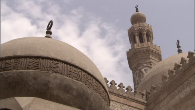 crescent finials rise above a mosque's domes and minaret. - minareto video stock e b–roll