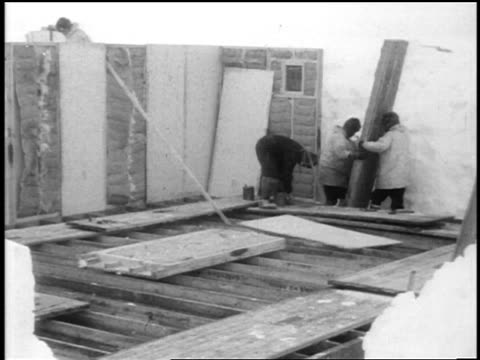 b/w 1928/29 crew building temporary shelter in ice on byrd's antarctic expedition / documentary - 1928年点の映像素材/bロール