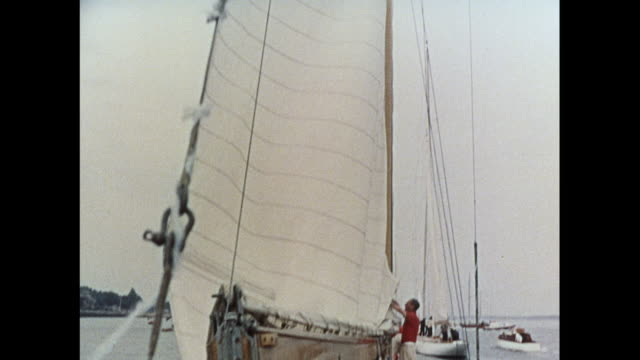 crew hoisting up the sail on a racing yacht in cowes / united kingdom - hoisting stock videos & royalty-free footage