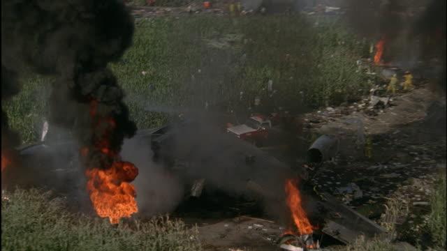 stockvideo's en b-roll-footage met aerial crew hosing burning wreckage of airplane - 1 minuut of langer