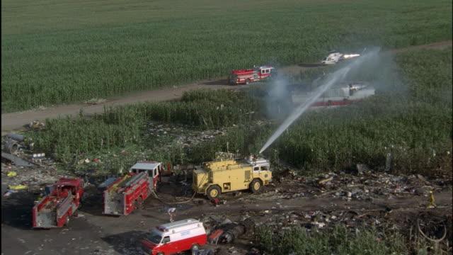 stockvideo's en b-roll-footage met ms, pan crew hosing wreckage of airplane - 1 minuut of langer