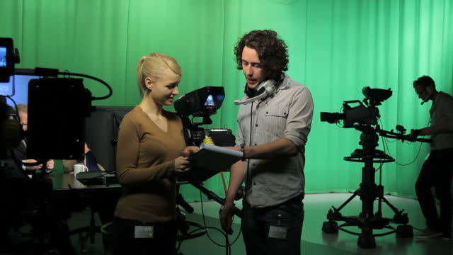 Crew in television studio discussing script