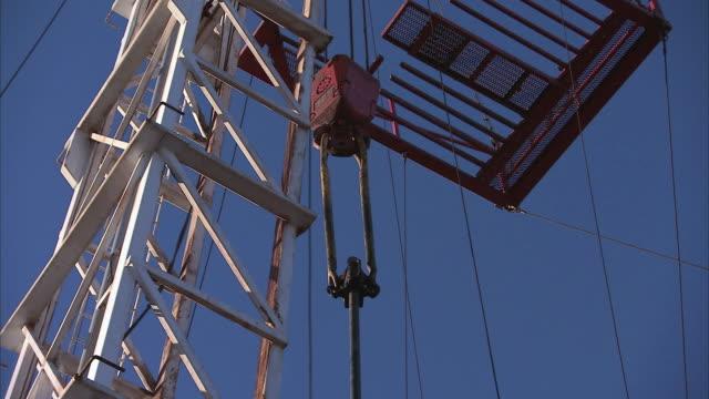 vídeos de stock e filmes b-roll de zi crew lifting and setting pipe into oil well using crane and pulley / texas, united states - rasto de movimento