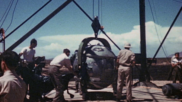 vídeos de stock e filmes b-roll de crew lowering the first atomic bomb onto scaffolding for test explosion / new mexico, united states - arma nuclear