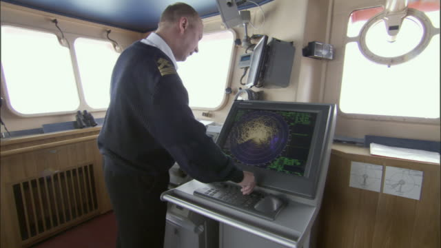 ms, crew member adjusting radar controls in navigation bridge, russia - ship stock videos & royalty-free footage