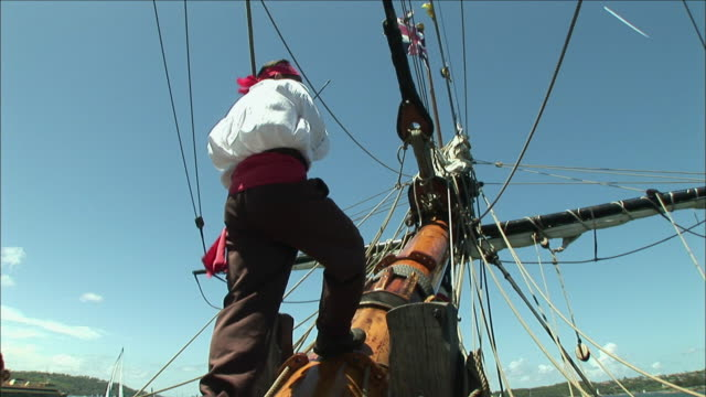 ms la tu td reenactment crew member of tall ship adjusting shrouds, sydney, new south wales, australia - seeräuber stock-videos und b-roll-filmmaterial