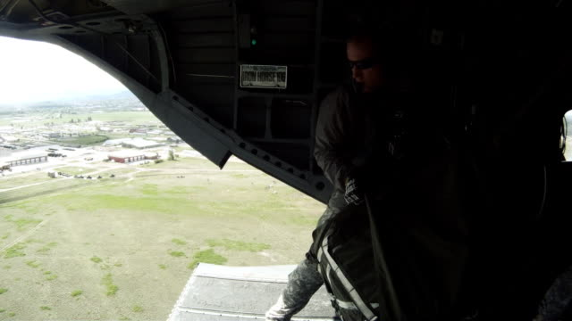 crew member on a ch-47 chinook helicopter adjusts something. - military helicopter stock videos and b-roll footage