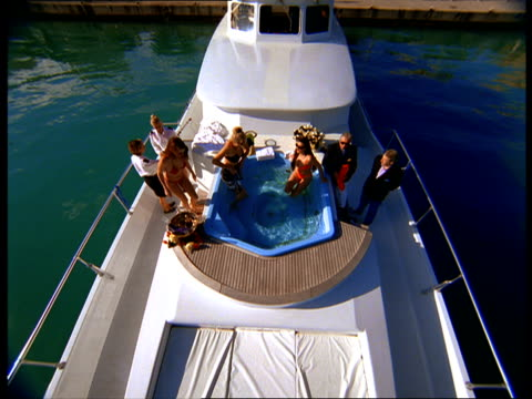 a crew member serves champagne to guests in a yacht's hot tub. - hot tub stock videos and b-roll footage