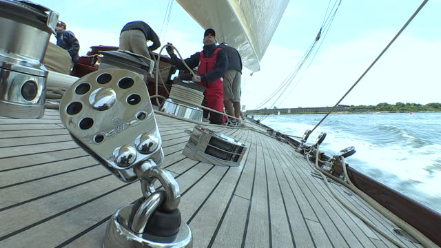 Crew members aboard the J Class Yacht Velsheda work together  on a hydraulic winch to pull lines that adjust the sails.