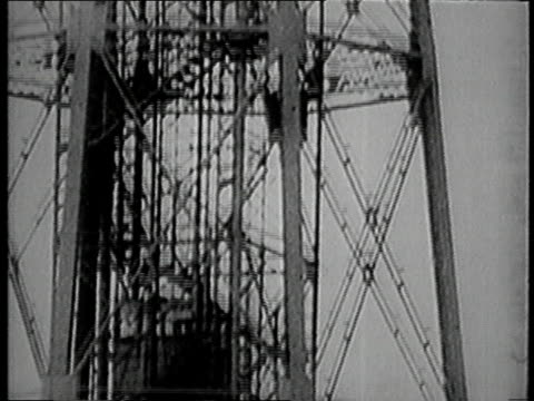 crew members boarding an elevator / elevator traveling to the top of a mooring and crew boarding the dirigible / dirigible flying away from its... - 1930点の映像素材/bロール