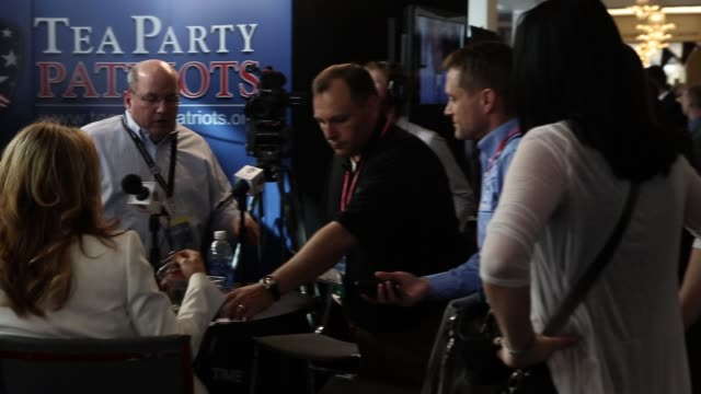 crew members of the tea party patriots prepare for a video shoot at their booth during the second day of cpac 2013 at gaylord national resort... - organisierte gruppe stock-videos und b-roll-filmmaterial
