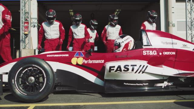 vídeos de stock, filmes e b-roll de membros da tripulação reparar o carro de corrida no pit stop - esporte de competição