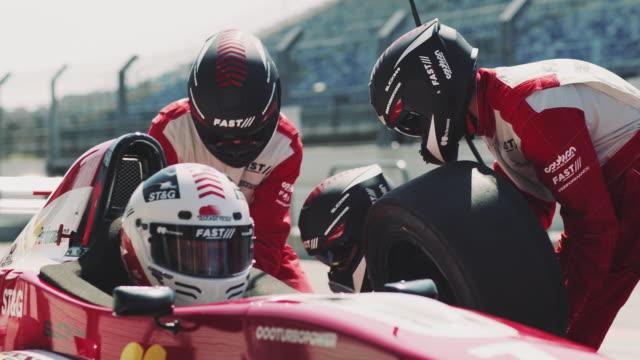 Crew members replacing tire of racecar at pit stop