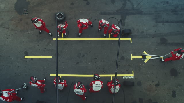 crew members waiting for racecar at pit stop - pit stop stock videos & royalty-free footage