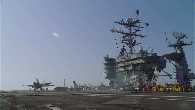 crew members watch as an f/a-18 hornet lands on an aircraft carrier. - 1999 stock videos & royalty-free footage