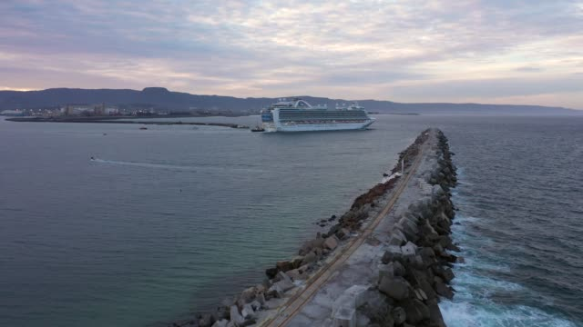 crew members wave from the ruby princess cruise ship as she departs port kembla on april 23, 2020 in wollongong, australia. australian border force... - cruise ship stock videos & royalty-free footage