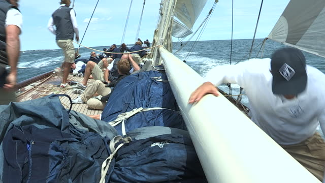 vidéos et rushes de crew members work to free a rope stuck under the spinnaker pole during a boat race. - équipage de bateau