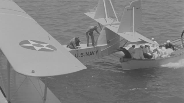 vidéos et rushes de  ms pan crew of men setting in boat and ocean attempting to unloading package to boat plane after boat plane taking off - marinière