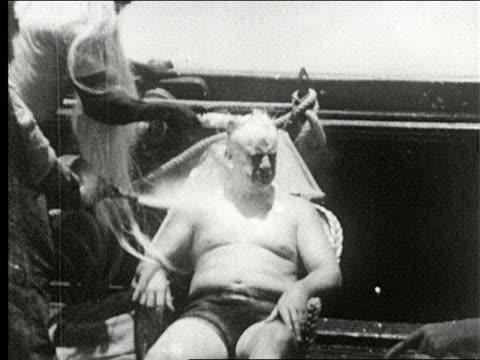 vidéos et rushes de crew of ship perform ceremony celebrating crossing the equator, man dressed as father neptune raises trident into air, man with long beard and pith... - rio de janeiro
