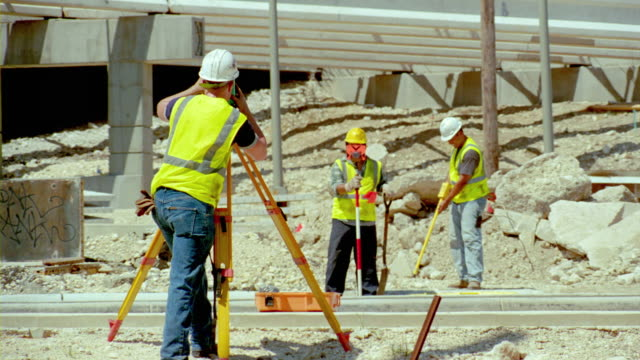 MS, crew of surveyors working at construction site, San Antonio, Texas, USA