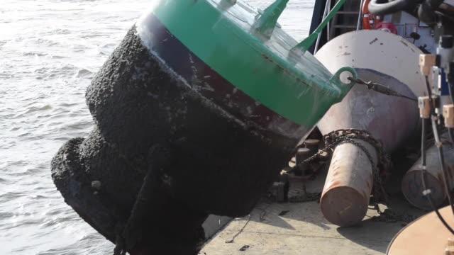 vídeos de stock e filmes b-roll de crew of the us coast guard cutter james rankin swap summer buoys for seasonal winter buoys in chesapeake bay maryland dec 12 2019 - ancora