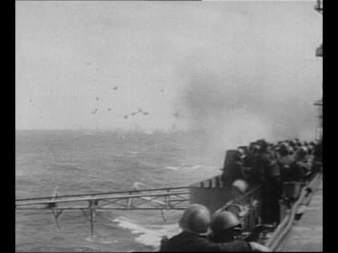 crew of uss franklin battles fire on its deck after japanese bombings / sailors on deck of other ship watch explosions on franklin in far background... - other stock videos & royalty-free footage