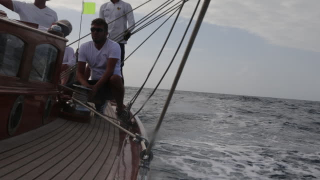 pan crew on deck as yacht moves fast at sea. - sailing team stock videos & royalty-free footage
