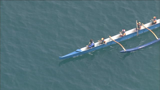 A crew paddles their outrigger canoe in the Sea of Japan.