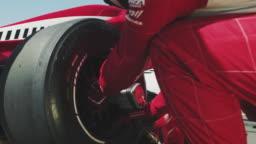 Crew replacing tire of racecar at pit stop