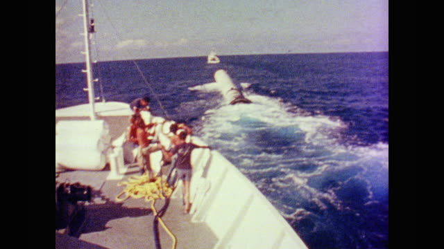a nasa crew retrieves the columbia's empty booster tank from the ocean - anno 1981 video stock e b–roll