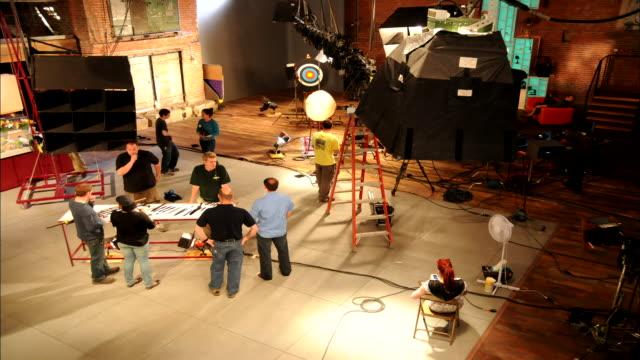 vídeos y material grabado en eventos de stock de a crew sets a stage for filming. - rodar