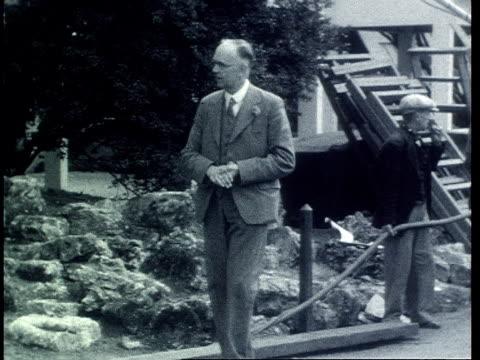 vídeos de stock, filmes e b-roll de crew setting up television camera and sound boom / camera crew film presenters c h middleton and elizabeth cowell touring the 1939 chelsea flower... - bbc